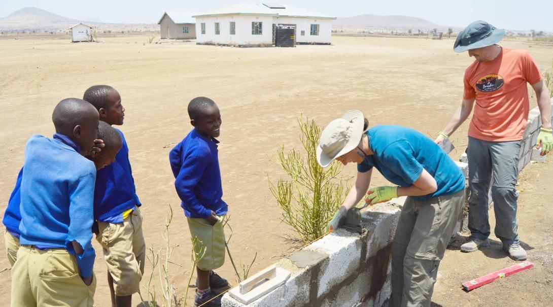 タンザニアの地元の子供たちが建築作業中のボランティアに話しかける
